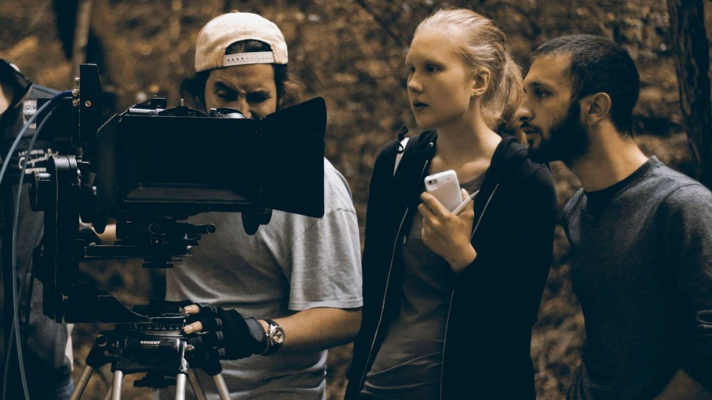 3 students check the images captured on the camera during an on location shoot.