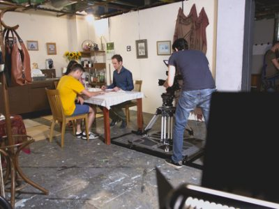 A camera operator captures a scene in the studio between 2 actors. The undressed studio space is obvious to the onlooker but will not be captured by the camera operator who is focused in the area of the studio dressed as a kitchen